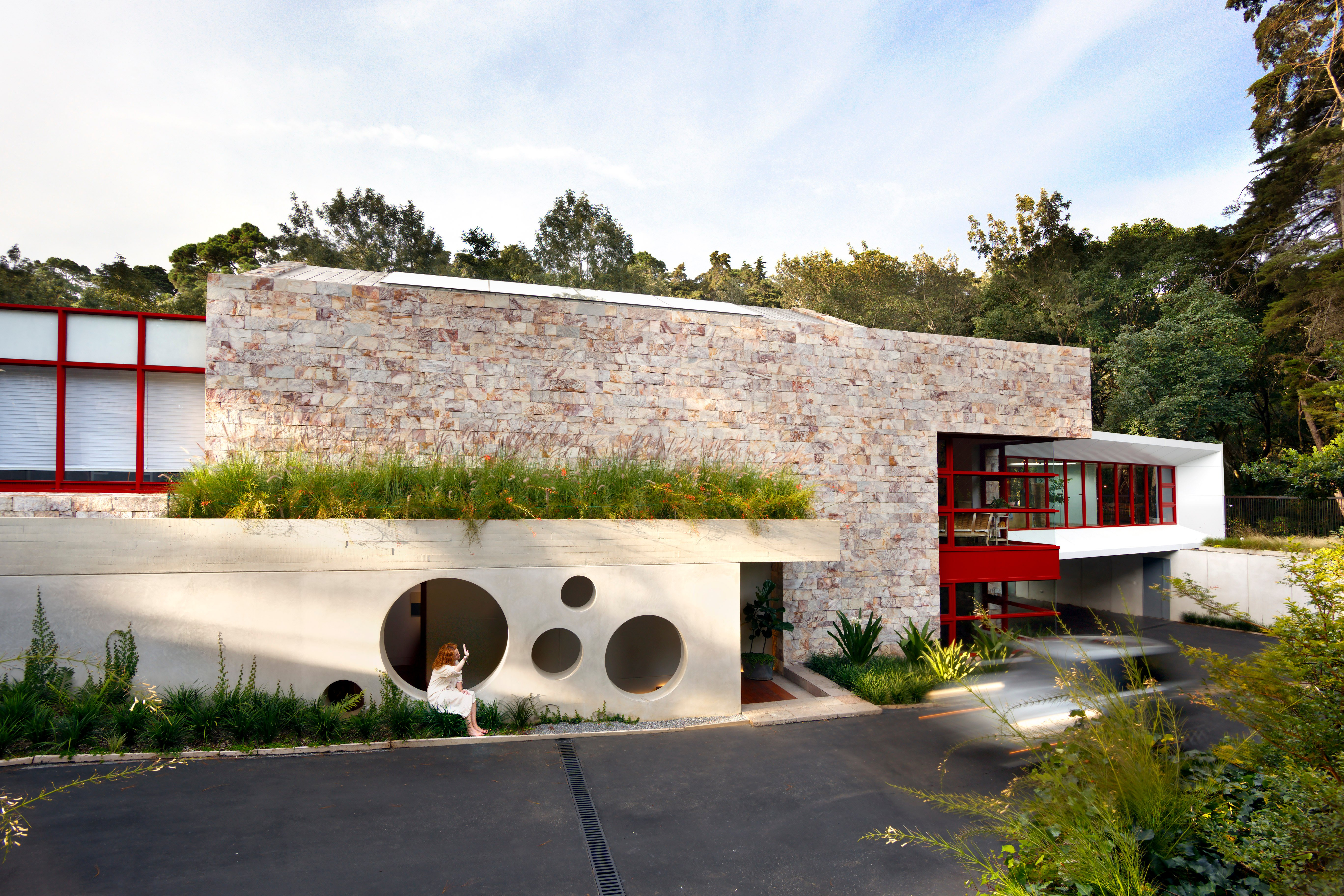 Seen from the front, the home is much more closed off and private, with a large unpolished stone wall dominating the view. Flanked by spreads of glass and red framing, we see a unique circular-cutout adorned entryway.