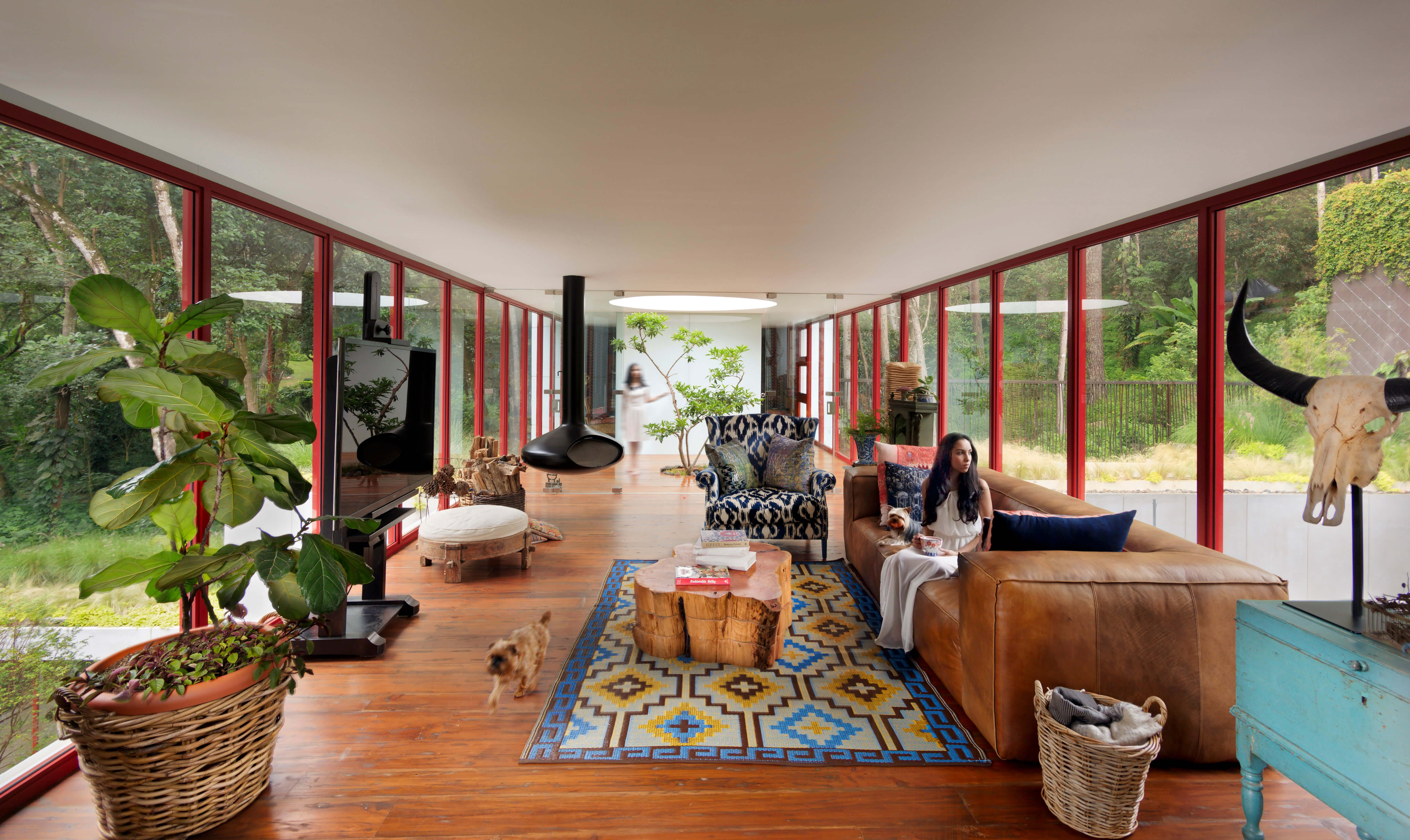 The lengthy, open plan space features a rich hardwood floor in contrast with the cool modern structure, and is filled with a versatile and personalized set of furniture. The plush leather sofa stands beside a tree-slab coffee table, surrounded by plant life and extraordinary views.