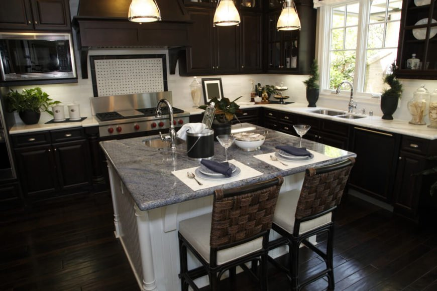 This kitchen balances its dark wood flooring and cabinetry with white marble countertops and matching tile backsplash, while the island truly punctuates the contrast. With white wood construction and grey granite countertop, the island features both a built-in sink and space for two diners.
