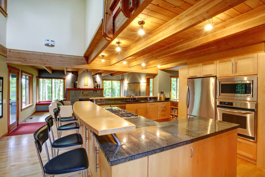 With a modern rustic look and open-plan design, this kitchen is absolutely awash in rich natural wood tones, from floor to ceiling. Exposed wood beams match the cabinetry and hardwood flooring, while the L-shaped island itself boasts an upper level dining tier of light wood. The large granite countertop includes room for a gas range and plenty of work space.