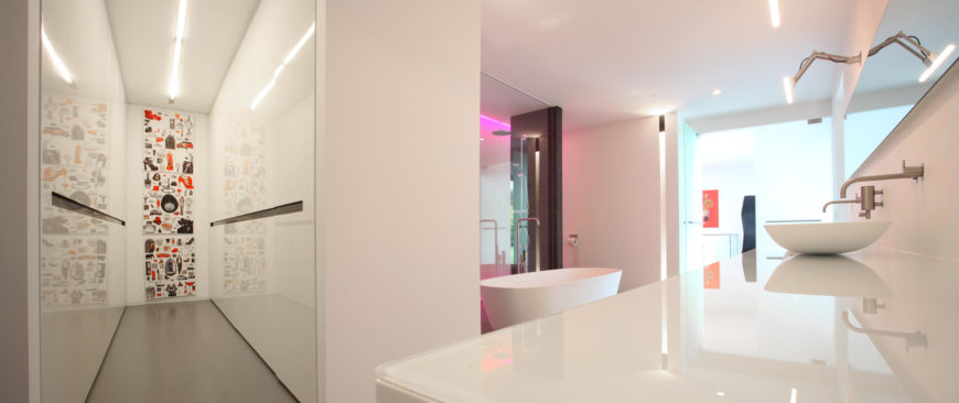 An angled view of the primary bathroom showcasing the color-changing neon lights in the shower area and a glass top counter with vessel sinks.
