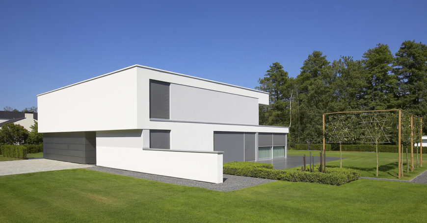 Standing over an expansive pristine green lawn, the house is wrapped in a subtle patio matching the grey shades of the exterior cladding. Shading seen at left provides incremental privacy.