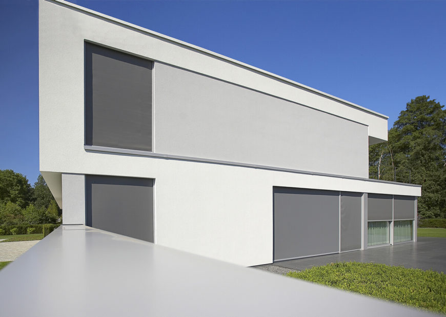 With shades drawn during the brightest part of day, the home becomes an almost monolithic slab of white and grey, concealing the intricate detail within and standing cleanly apart from the surrounding forested landscape.