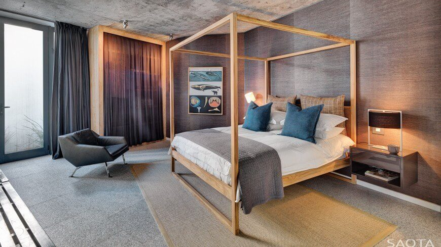 The thin light wood frame of this four poster bed draws color from the natural fiber area rug and a curtained light wood closet. The rest of the room is in darker shades.