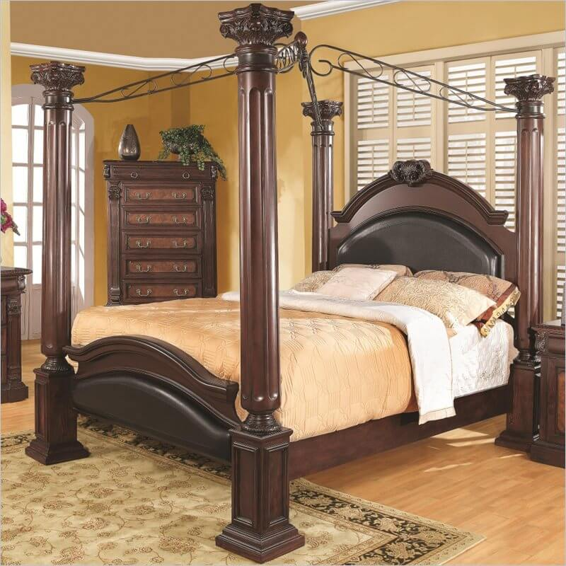 A stately four poster bed in rich dark wood and leather inlays. Wrought iron bars create an X above the bed and add a lighter element to this heavy, imposing piece.