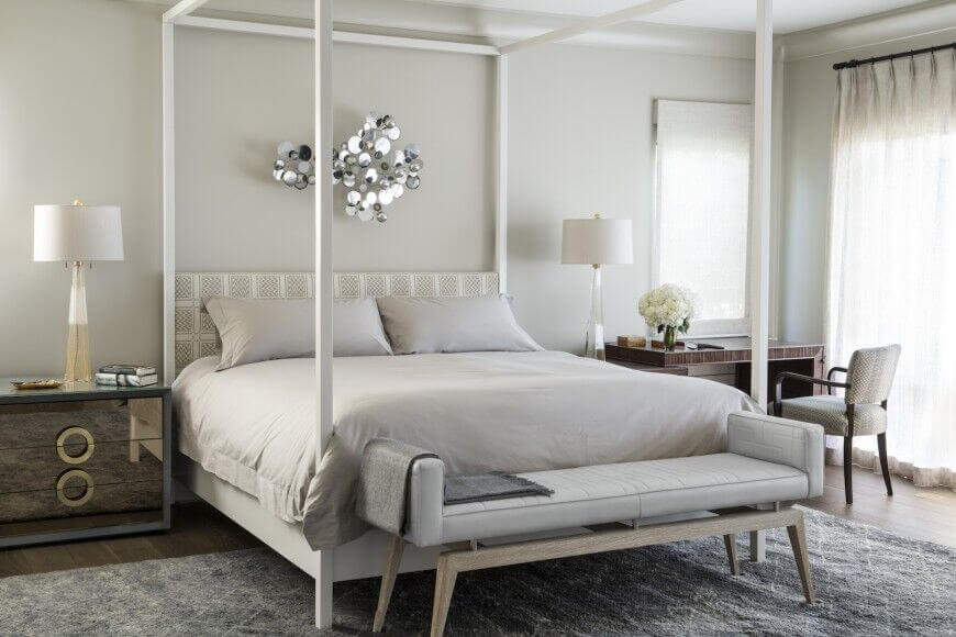The thin white posts of this four poster bed draw attention to the large bed and add visual interest and light contrast to the light gray walls. Mirrored night stands and a small desk add further texture and light to the room.