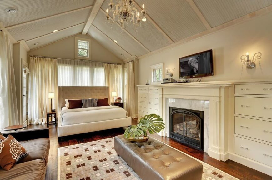 This gorgeous room is bedecked in neutral beiges and complementary earth tones. The wall mounted TV is nestled above the fireplace flanked by drawers on either side. Facing the sofa rather than the bed, this design seems to reflect the owners need for an additional living space.