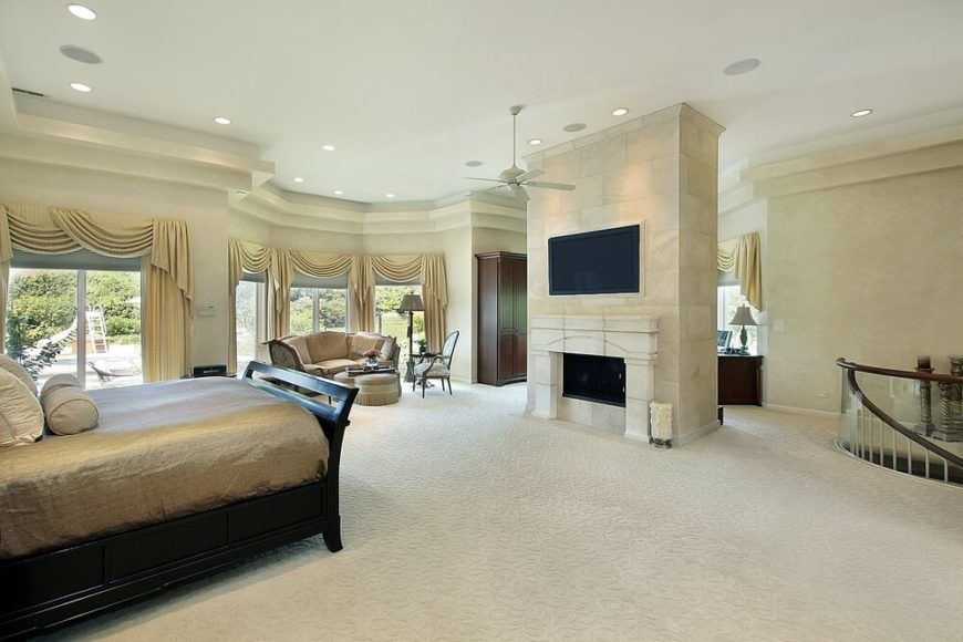 This luxurious cream and gold bedroom features gorgeous ceilings, furniture, drapery, and just a glimpse of a spiral staircase. The television is mounted above the fireplace in an elegant stone structure, and can be viewed perfectly from the dark hardwood bed.