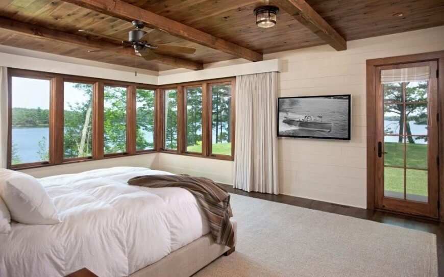 A wall mounted flat screen in a simple bedroom. A large cream area rug sits atop hardwood flooring. Natural, rustic beams are utilized for added interest to the ceiling, and beautiful views of the lake are apparent through the numerous wood framed windows.