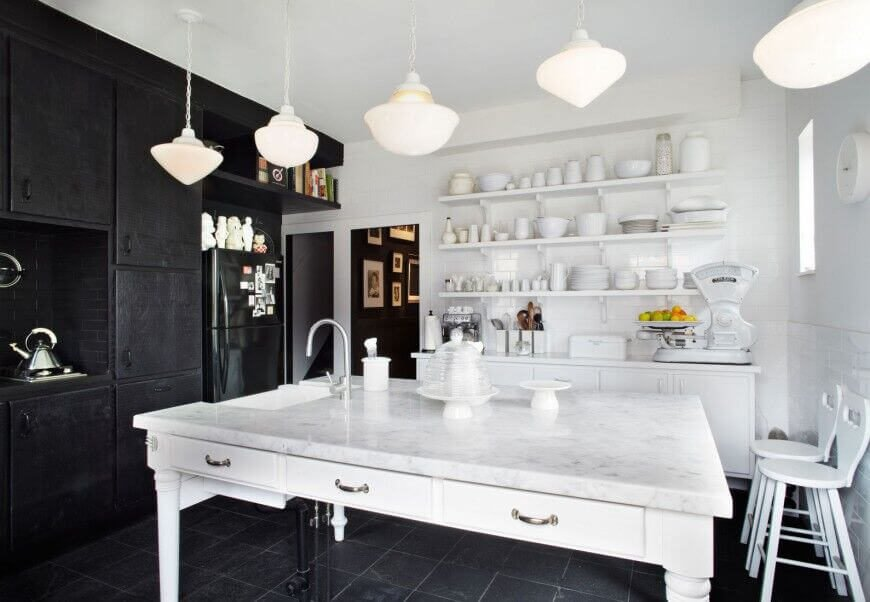 White and black strike an amazing contrast in the design of this kitchen. Ebony cabinets and backsplash, along with appliances and the tile floor, are mixed with an all-white marble island, open shelving, and walls.