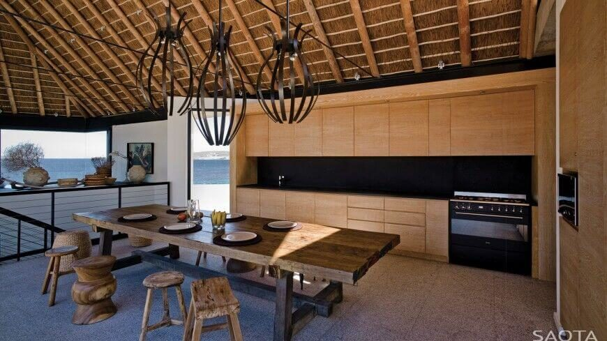 The sleek black range of this kitchen seems to merge into the countertops and backsplash, which are a perfect match. This kitchen is a combination of minimalist and rustic design. The stools at the table are all utterly different.