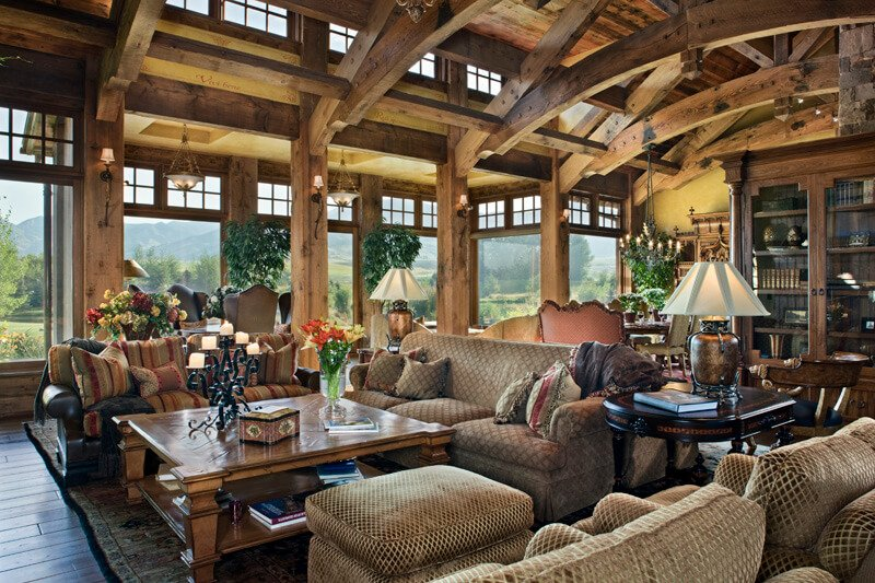 This rustic dark wood living room has two large seating areas and fantastic exposed beams across the wide, tall ceilings.