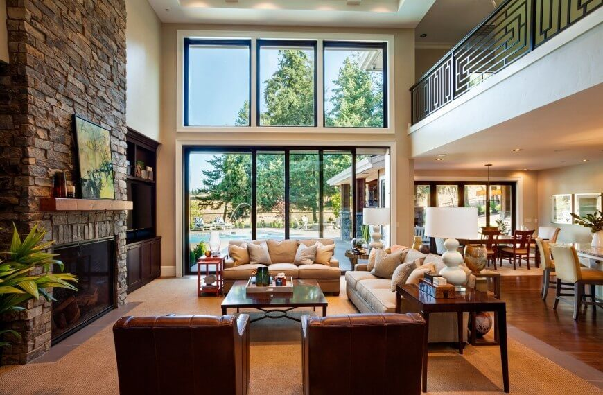A wonderful brick stone fireplace overshadows the above living room, which is rich in browns, tans, and creams. White accent pieces tie into the dining area of this open concept home, while a wall full of windows allows natural light to envelop the area.