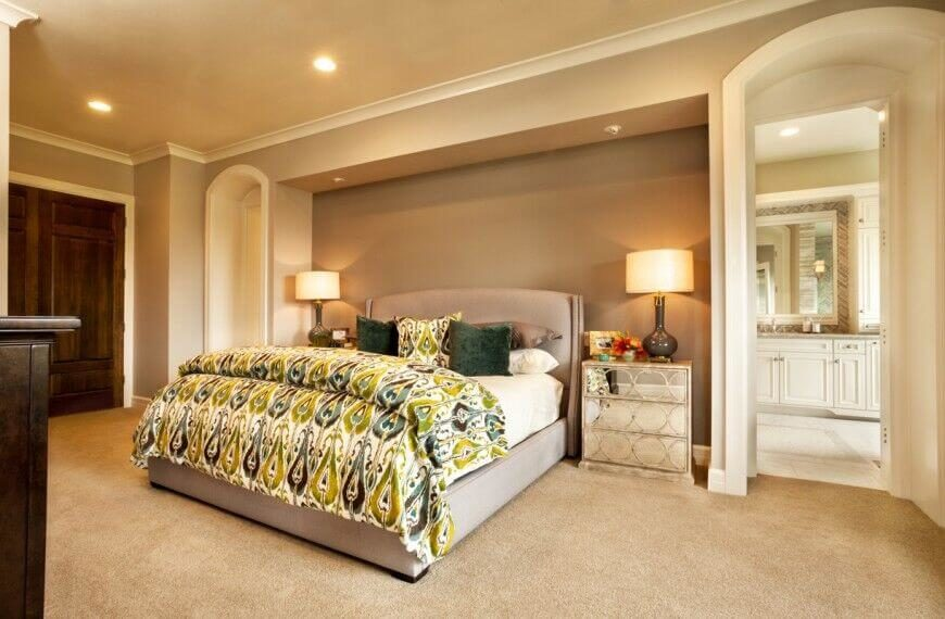 This gorgeous bedroom has a large bed in the center of the room. This fabric headboard is a neutral taupe color, and contrasts with the playful patterned green comforter and pillows.