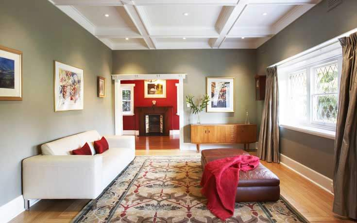 Absolutely gorgeous coffered ceilings with recessed lighting bring elegance to this small living area. Sage walls bring traditional neutral comfort to the room, while the bold red accents tie in with the large area rug and the adjoining crimson entranceway.
