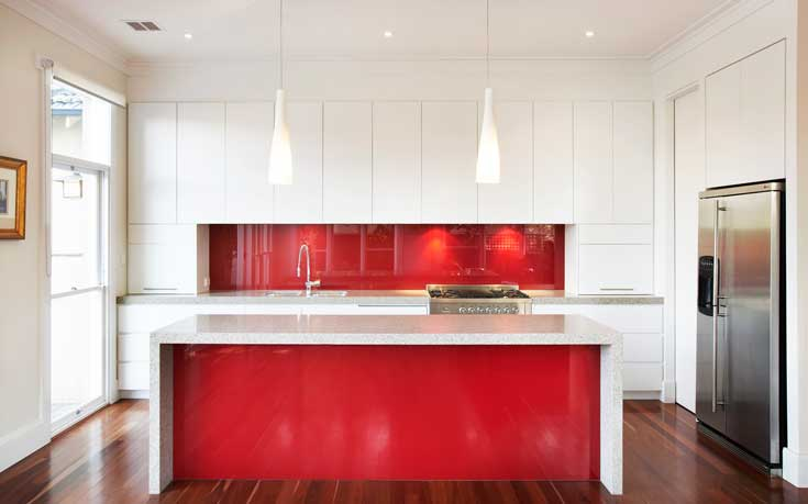 This glossy modern red kitchen with stainless steel appliances and bright white cabinetry is as beautiful as it is functional. The candy apple red island matches the vibrant backsplash, and is perfect for preparing family meals.