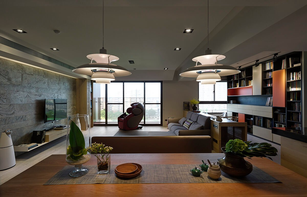 Viewing the entire open space from over the dining table, we see a broad array of textures and tones, united by the themes of natural stone, wood, and sharp edged metallic flourishes. The full height windows spill ample light into the room.