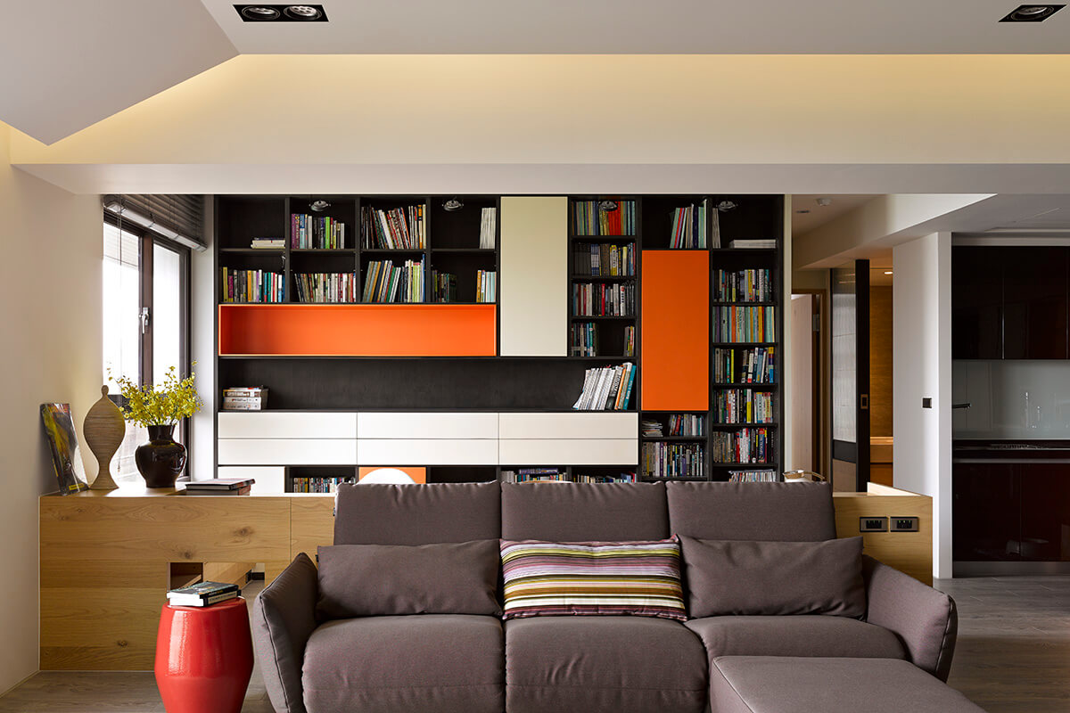The low-slung modern sofa complements the neutral hues of the home, and is backed against an innovative desk design, acting as a room divider within the open floor plan.