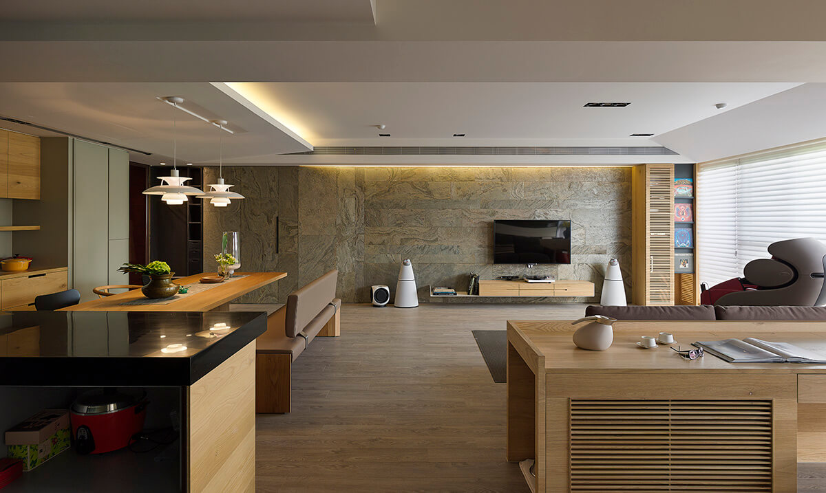 Viewing straight down the center of the home, we can appreciate the unifying elements of rich natural wood and stone, tying the wide open space together.