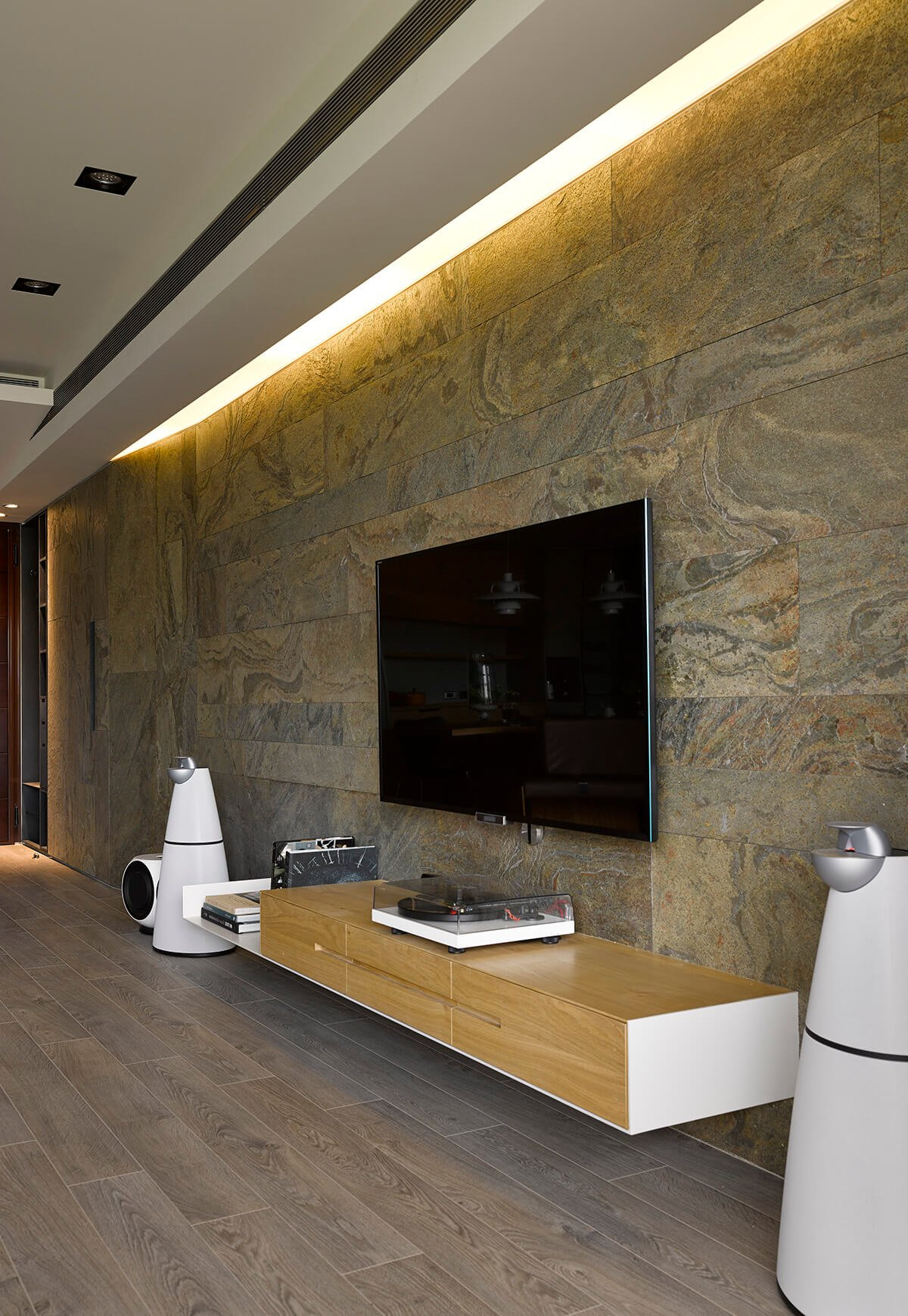 Because so much of the design here stems from the owner's preferences, we see the inspiration appearing in tangible form across the home. Here, a high end turntable sits below the television, a sharply designed instrument reflecting the values behind the home itself.