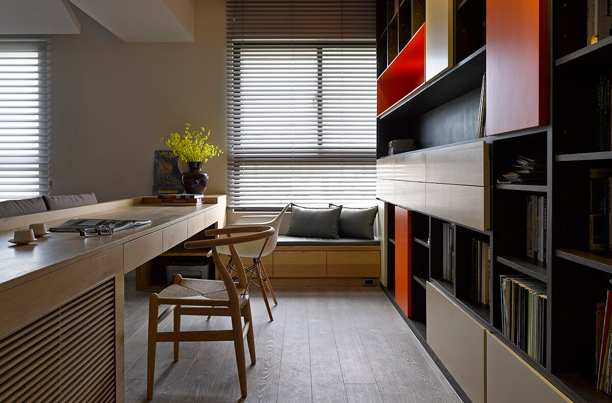 The home office itself features a discreet window bench seat in natural wood, with built-in storage. The lengthy desk houses enough workspace for two people, flanked as it is by a pair of mismatched modern chairs.