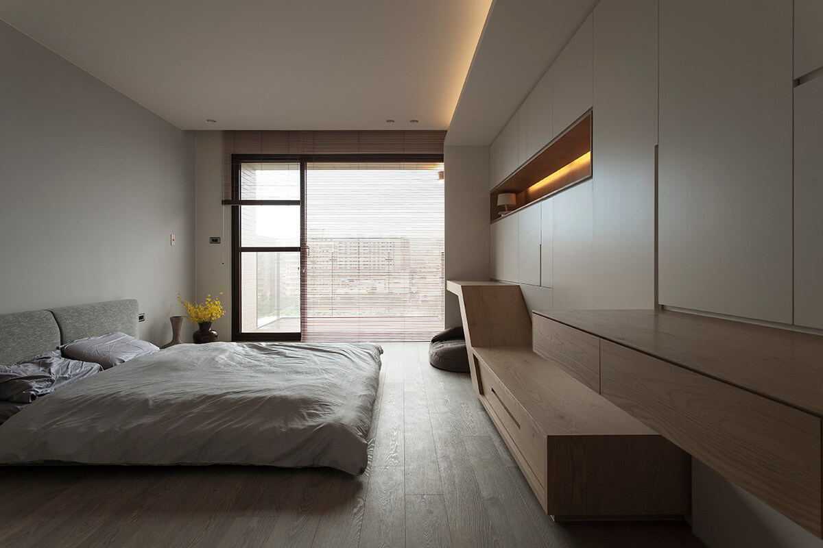 The contemporary primary bedroom features a gray floor bed facing the built-in wooden shelves and storage cabinets.