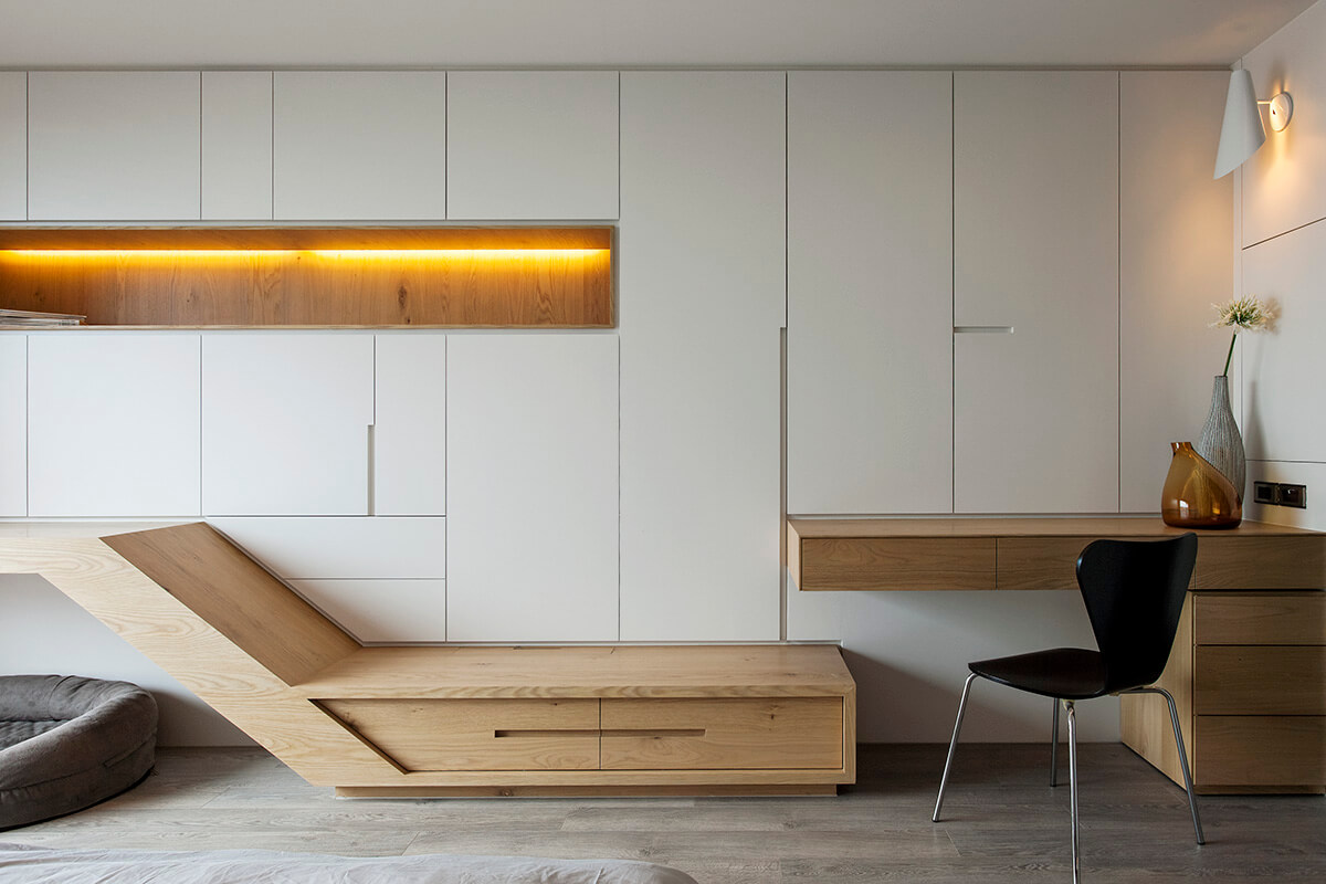 In addition to the uniquely cut white panels, the wall features a recessed shelf in natural wood, with lighting built in. The desk at right fits neatly into the minimalist design, lining up perfectly with the storage platform.