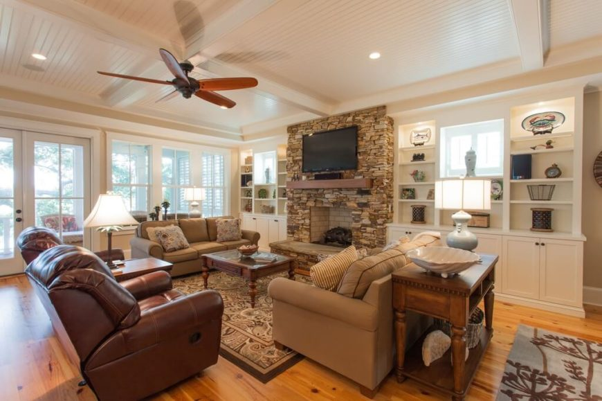 This ceiling fan offsets the white ceiling and accents the warm brown tones of the room. The use of wood fan blades adds to the natural look brought to the room by the stone fireplace and beautiful wood floor.
