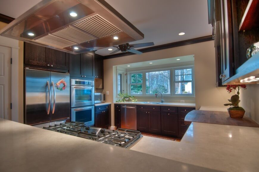 The G-shaped countertops clearly define this cozy kitchen, stuffed with rich wood cabinetry and white marble countertops. A large cutting board segment is built into the counter at right, complementing the built-in stainless steel range at left.
