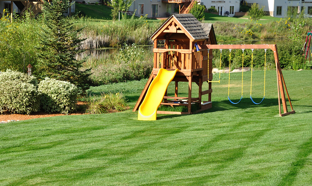 A wooden play area with a slide and swingset. Below the cabin area is a small picnic table.