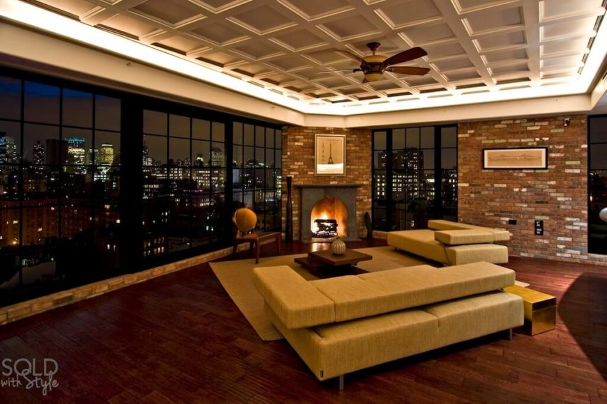 The ceiling fan perfectly complements the use of warm wood and yellow tones in the furniture while standing out against the white recessed ceiling with recessed lighting.