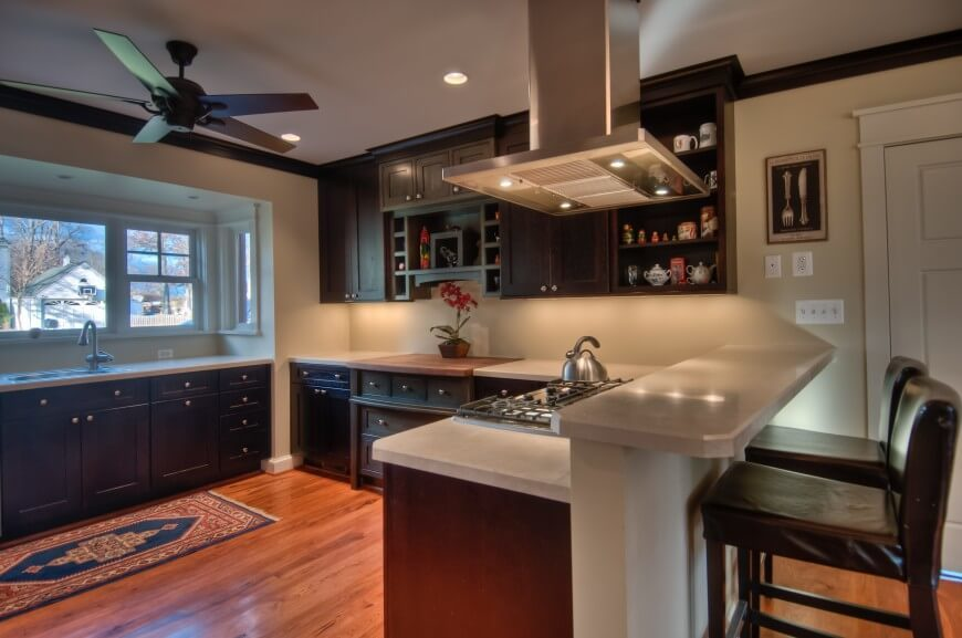 Seen from a new angle, we can appreciate the raised tier at right, providing in-kitchen dining for a pair of leather upholstered bar stools. The warm hardwood flooring and large bay window add warmth to the space, while sets of open shelving offer a space for artful nicknacks.