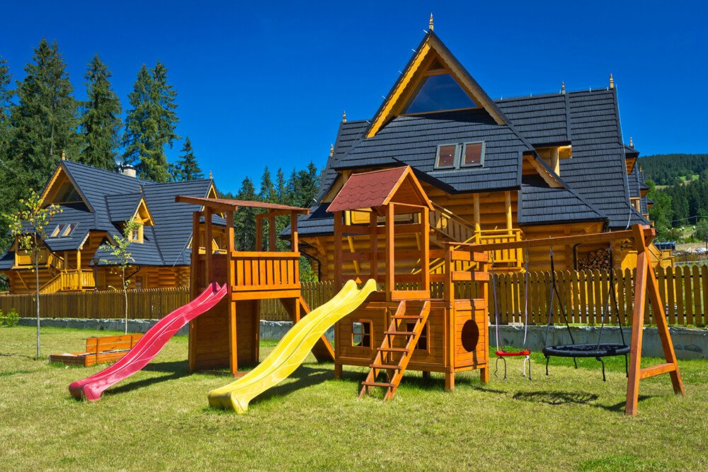 This playset has a couple of unique swings, along with several slides, a climbing wall, and an enclosed section with portholes.