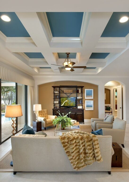 Every color choice in this room is carried throughout by subtle touches. The heavy, dark wood of the furniture is also seen in the fan, the gorgeous blue tone is carried up into the recessed ceiling, and the golden yellow is in the lamp and the chair.