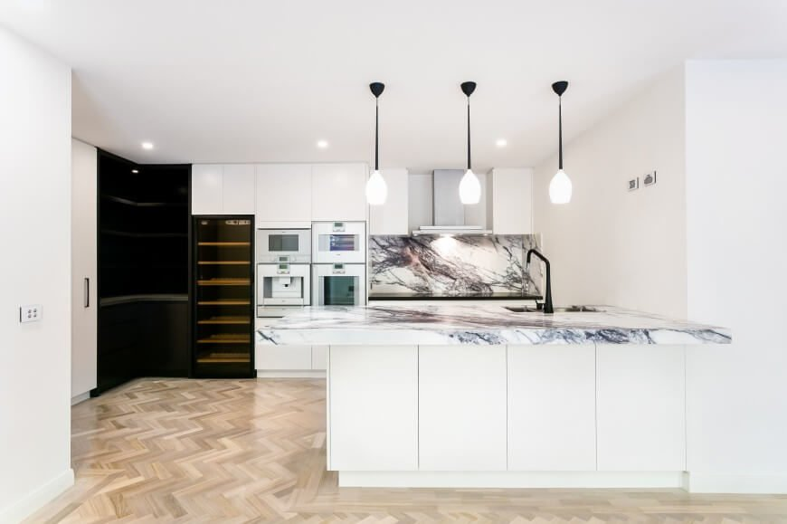 Pristine white, hardware-less cabinetry defines this ultra-modern kitchen, with a splash of high contrast provided by black shelving in the corner. Thick slab marble countertops and a matching backsplash boost the visual appeal. The plumbing, far countertop with modern range, and trio of pendant lights all echo the contrast in their black framing.