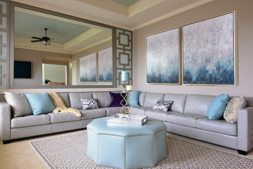 The dark color of the ceiling fan in this room offsets the pale silver of the couch and wall art and the accent blue seen throughout the room.