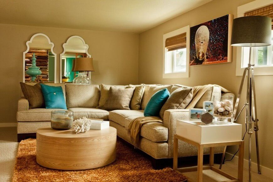 This gorgeous and cozy family room uses bright turquoise accents to add color to the room, in the mirror reflection one can see that the same color is utilized in other parts of the house. The thick rug offsets the neutral hues of the room and allows the lovely round coffee table to stand out.