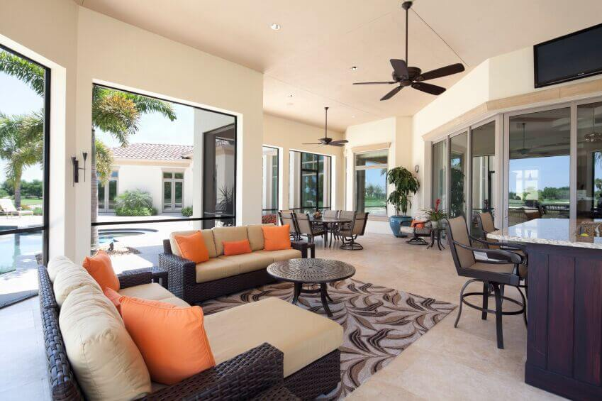 The ceiling fans in this living room match the use of dark wood throughout the room and allow the fan to stand out against the pale cream of the walls and ceiling without distracting from the rest of the room.