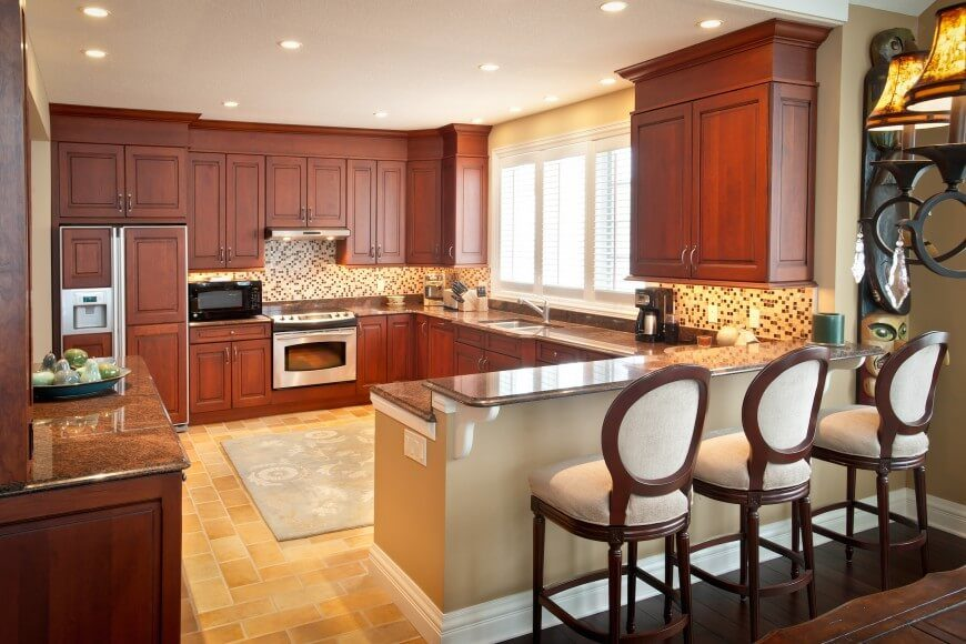 Traditional style informs the rich wood cabinetry and light tile flooring of this kitchen. The brown granite countertops reach out toward a two-tiered wing, with raised surface for in-kitchen dining. Intricate micro-tile backsplash, sandwiched between the wood cabinetry and countertops, act as a playful counter balance to the room.