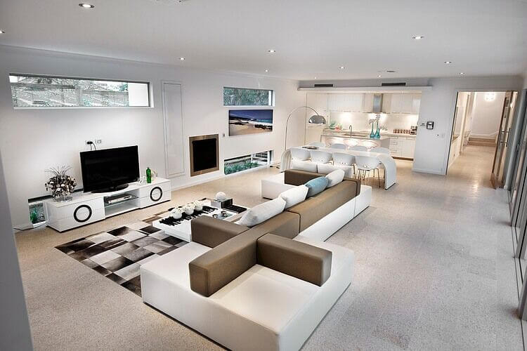 The most stunning part of this living room is the enormous modular sofa, which allows the seating to face either way, depending on the need. To the rear of the room is a small white kitchen with a dining area between the two.