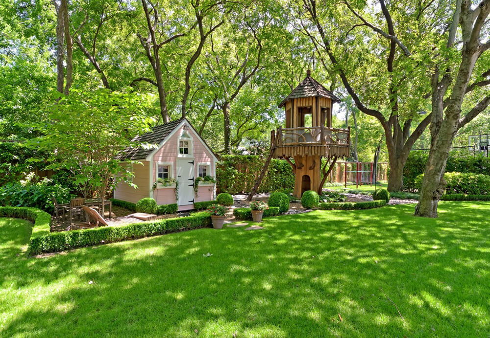 A small fairy cottage has its own garden and landscaping, with a treehouse tower off to the right. The railing around the top of the tower has bent wooden designs.