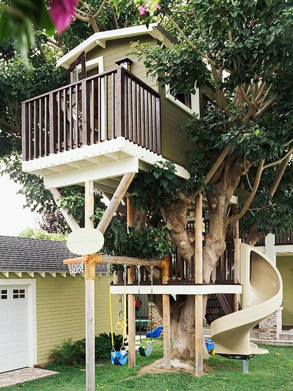 This fantastic, multi-level treehouse features a large spiral slide, a swing set, basketball hoop, balcony, and a spacious finished interior.