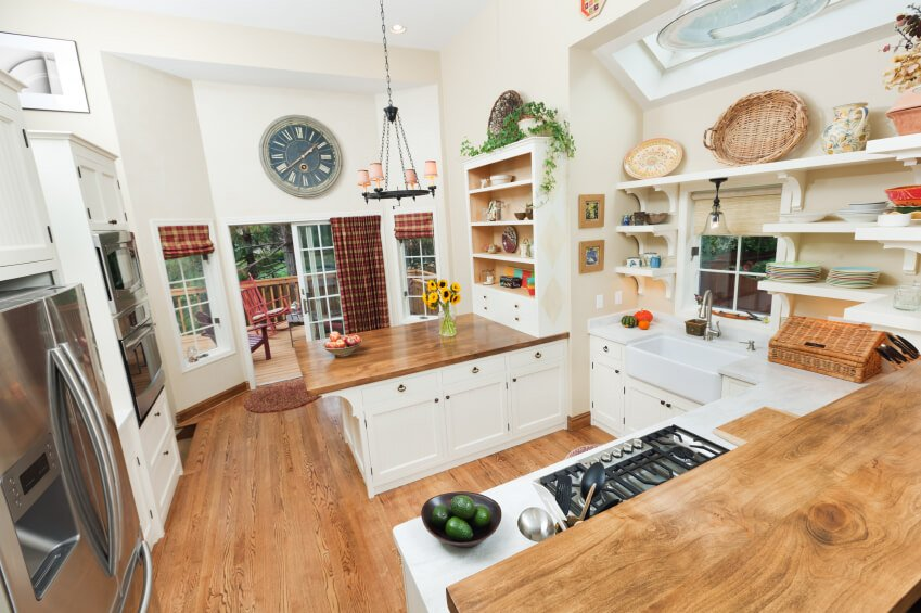 This sprawling kitchen is packed with detailed and useful elements, from the ample shelving to the large countertops in both sleek white and rich wood. The design allows for the white cabinetry to be spaced well, offering abundant space for movement. The central hardwood countertop brings a wealth of workable space and doubles as an in-kitchen dining table.
