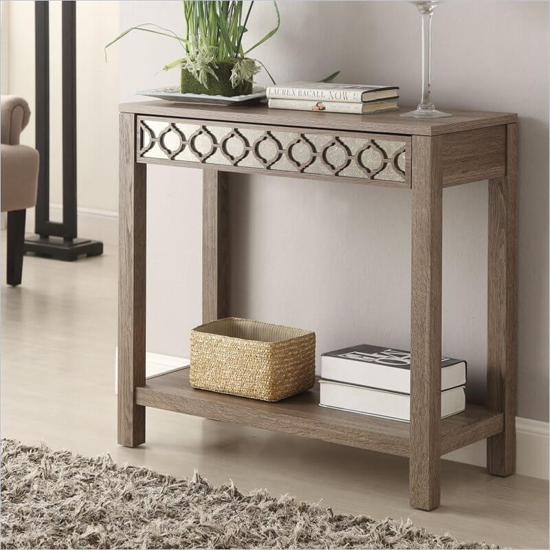 A reflective surface beneath the repeating pattern on the front draws the eye to this table, which has a prominent wood grain and a silvery color.
