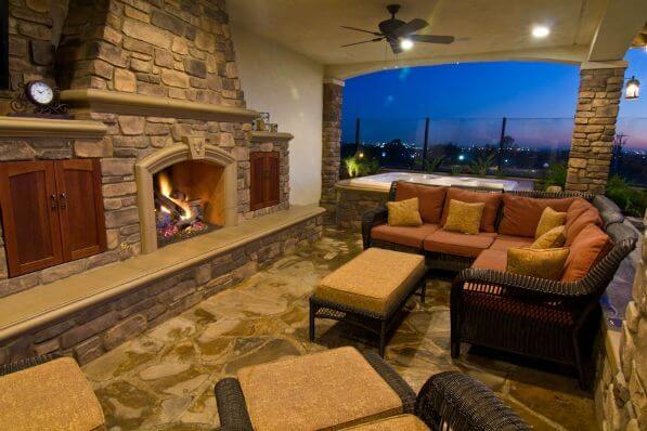The fan on the lovely patio matches the dark wicker furniture. The stone work around the fireplace is mirrored in both the floor and the surrounding half wall.