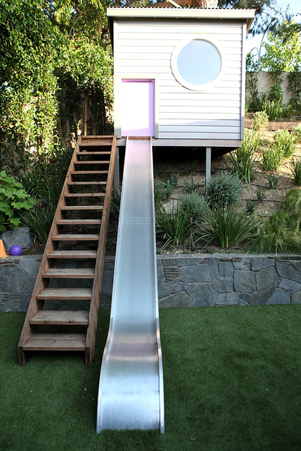 A long set of stairs leads up to a playhouse up on a hill. A metal slide leads down from a light pink door into the lush yard.