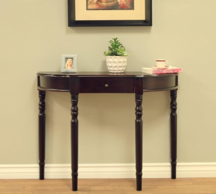 This half-circle table has a single drawer and is in a rich dark wood. The bowed design is sleek and delicate, with long, slim legs.