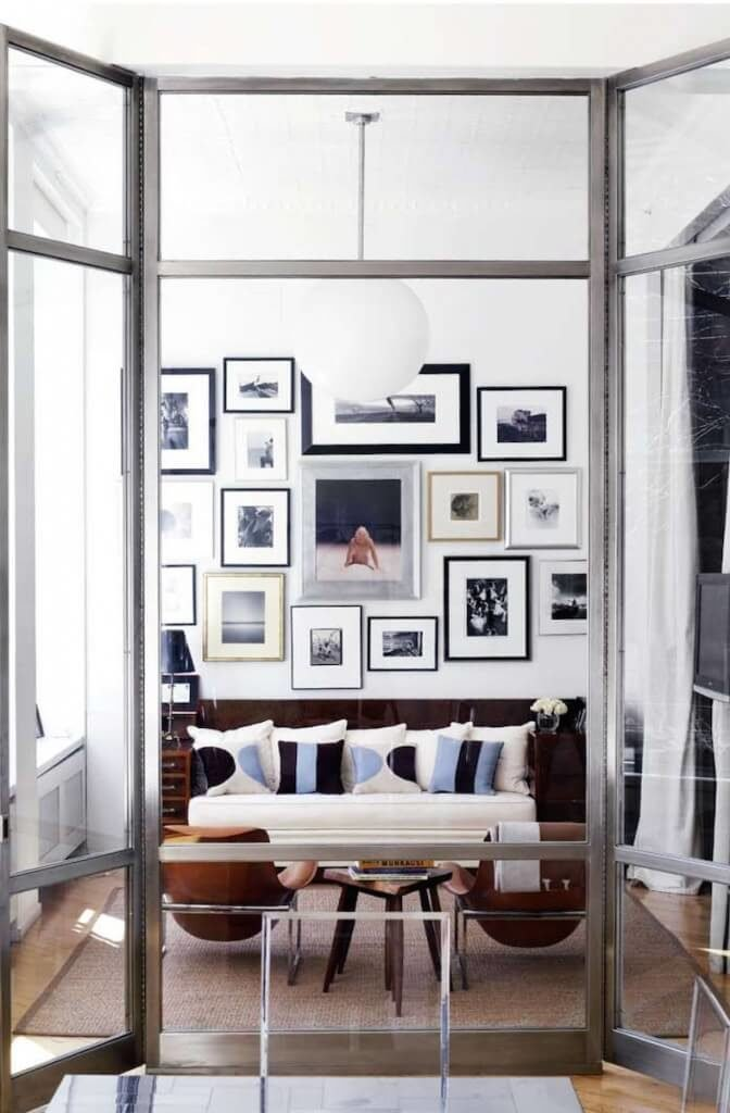 Cool tones are warmed up by the inclusion of rich brown in the furniture. Splashes of light and navy blue create interest against the monochromatic wall collage.