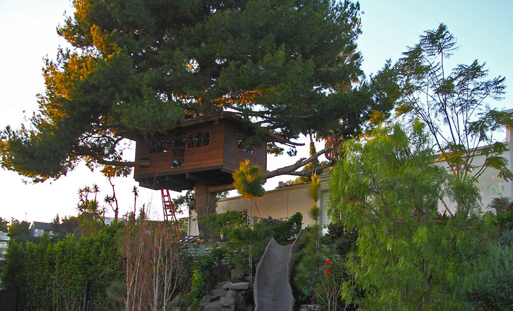 This spacious treehouse is built into an enormous tree. A faux stone slide is built into the hillside as well to create an adventure play area.