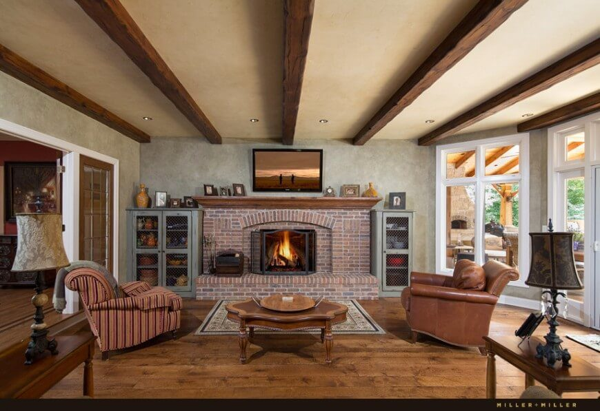 The living room in whole, large windows illuminate the space, revealing the marvelous brick fireplace and exposed ceiling beams. Faded blue cabinets with mesh fronts supply great storage while the color complements the walls well.